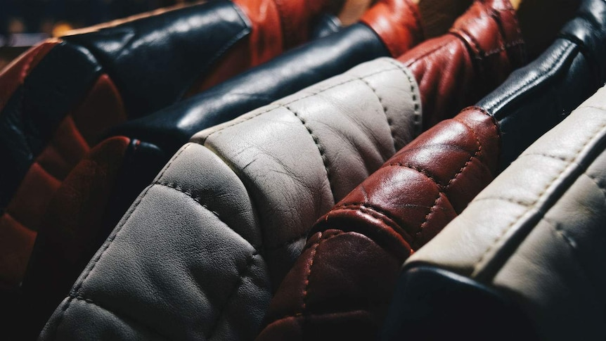 Close up of leather jackets in brown, black and grey on wooden coat hangers.