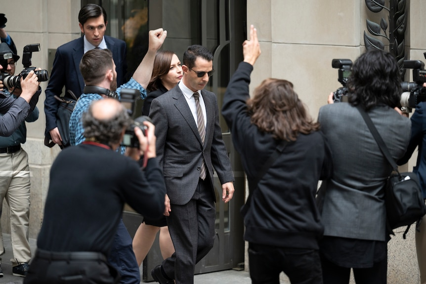 Jeremy Strong, in character as Kendall Roy in season 3 of Succession, is surrounded by photographers while walking down stairs