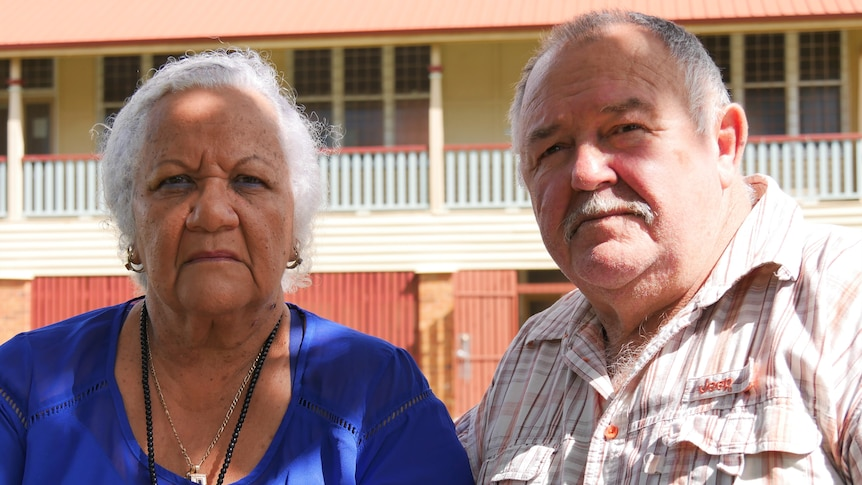 An elderly south sea islander woman sits next to an elderly white man. They look upset