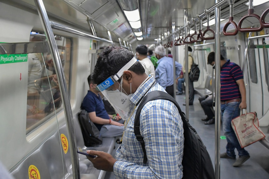 The interior of an Indian metro train with commuters wearing PPE.