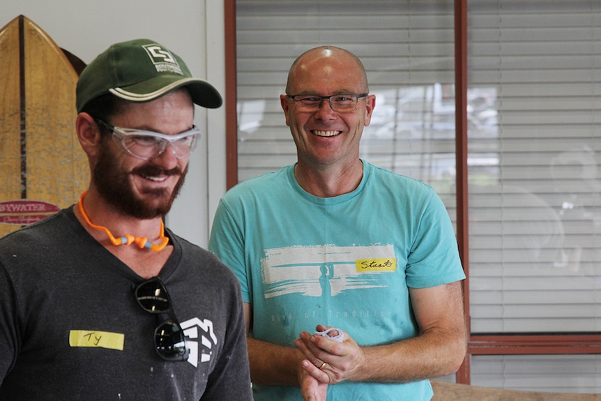 Two men smiling and laughing in a workshop with a surf board in the background.
