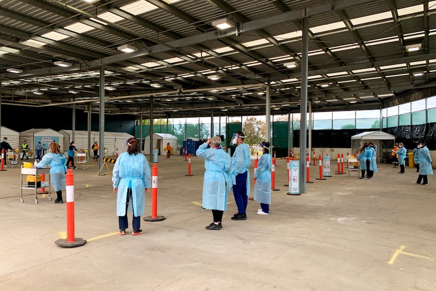 Healthcare workers in full PPE wait for cars to arrive at a drive-through vaccination site.