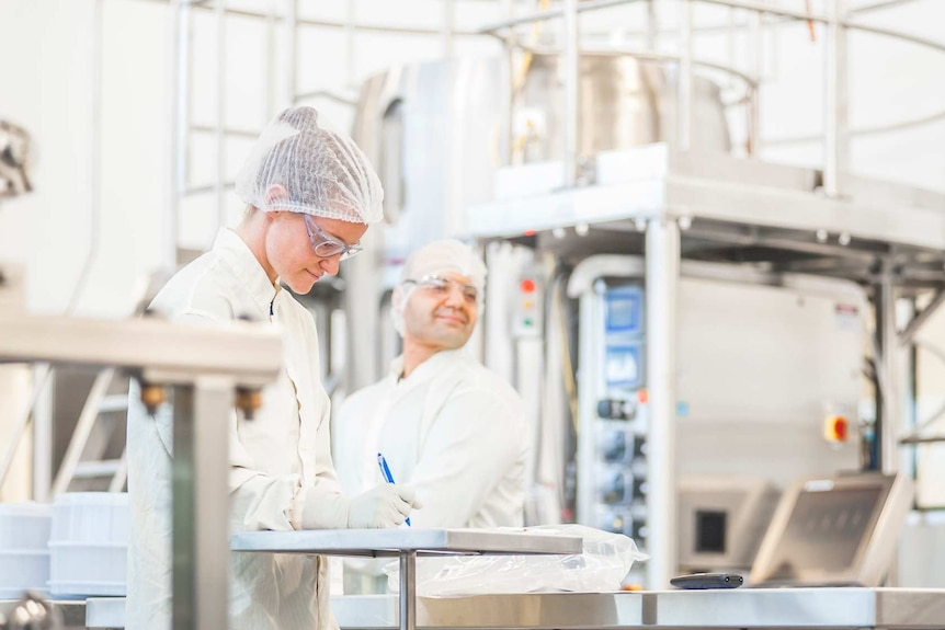 two people in white protective equipment stand in a laboratory