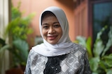 A head and shoulders shot of Siti Musdah Mulia. She is smiling against a balcony background.