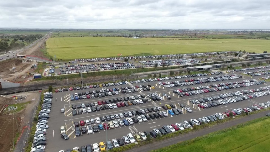 A drone shot of a large car park, filled with cars, near a train station and some green fields.