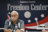 """A man sits at a desk in front of a sign that reads """"Catoosa County Freedom Center""""."""