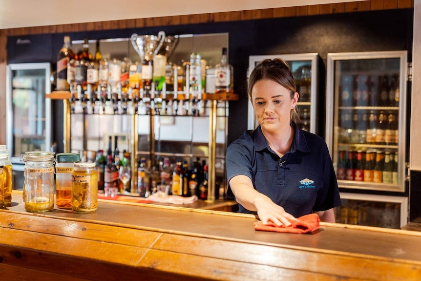 Brooke Littlewood wiping down a counter in a bar at the Eucla Motel.