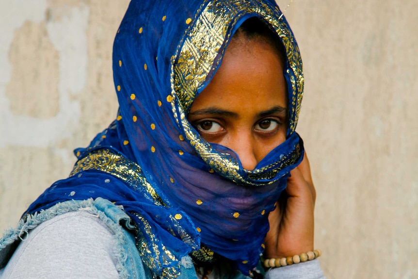 A woman in a blue and gold scarf wrapped around her face