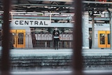 a masked woman checking her phone while standing on a train platform