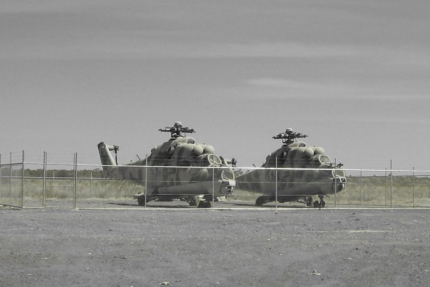 A black and white photo of two Mil Mi-24 Hind attack helicopters on the ground.