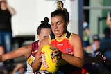 Ebony Marinoff controls the ball for the Adelaide Crows while in front of a Brisbane Lions opponent.