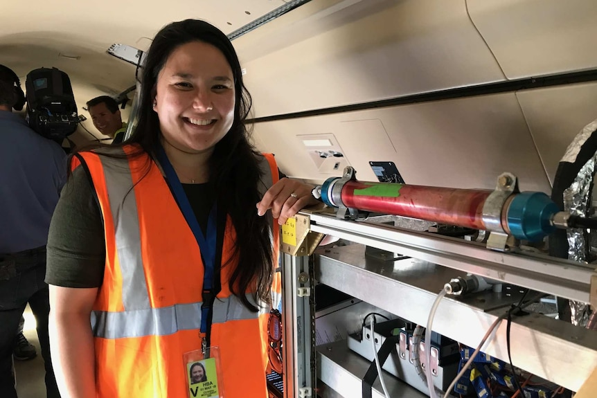 Christina McCluskey from National Centre of Atmospheric Research monitors a cloud-inspired machine on board the aircraft.