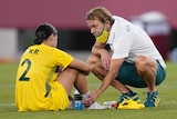 Tony Gustavsson crouches down to console Sam Kerr, who is sitting on the ground and is sad