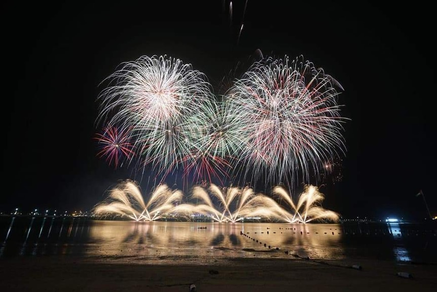 numerous gold, purple and green fireworks being fired into the air and off the ground at night