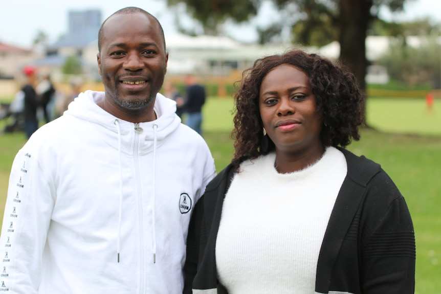 Fama Toure's parents Sekou Toure and Aramatu Sangary smiling at the camera, standing on a local grass oval.