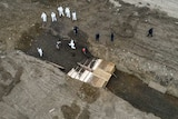 workers in white and black protective clothing dig a large grave with coffins inside