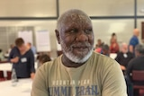 A portrait shot of an older Aboriginal man with short gray hair and a beard, he has his arms folded and is wearing an olive colo