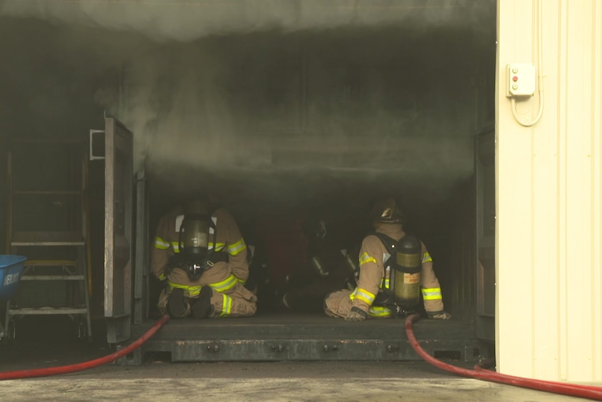 Firefighters site inside a shed with smoke coming from it