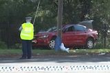 A police officer stands in front of a car that has been damaged in a crash
