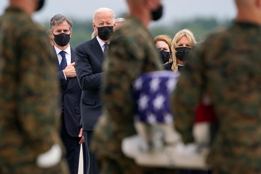 US President Joe Biden, first lady Jill Biden  look on as as a carry team moves a transfer a coffin wrapped in the US flag.