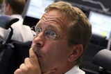 A trader looks worried as he sits at his desk in front of the DAX board at the Frankfurt stock exchange