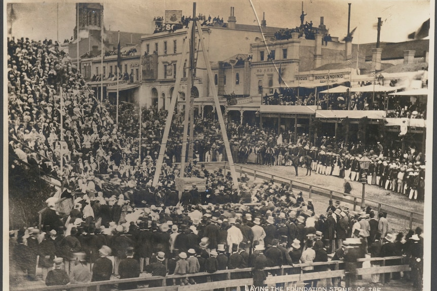 A black and white photograph shows a crowd of people watching on Prince Alfred lay the foundation stone at Melbourne Town Hall.