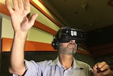A man wearing a headset stretches out his hand.