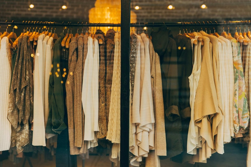 A rack of clothing in a store, mostly jumpers and autumnal knits.