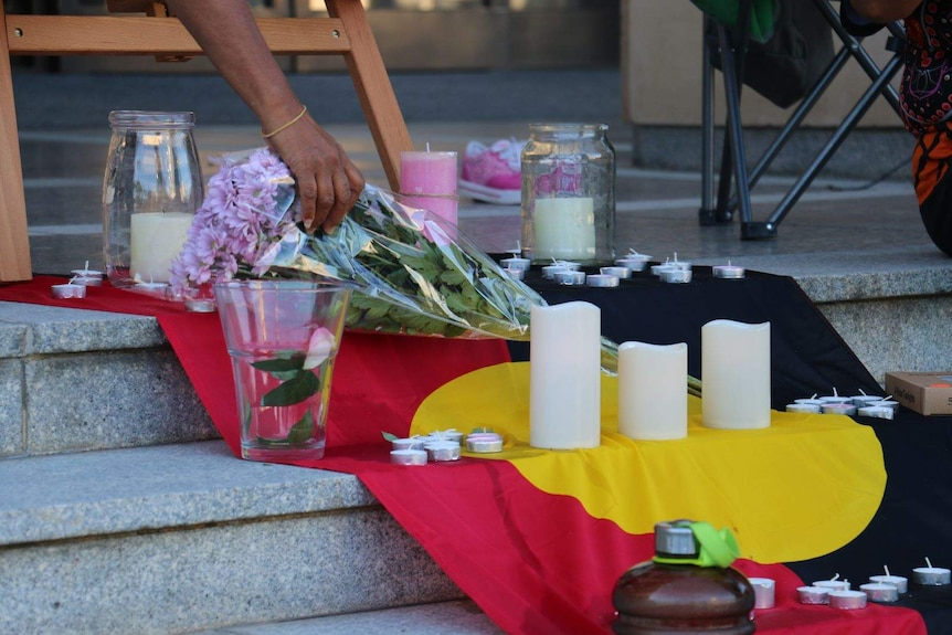 Flowers and candles at a vigil for Annaliesse Ugle.