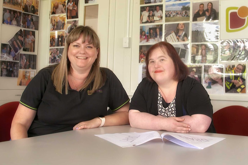 Two women sit at a desk; a sign behind reads 'ACT Down Syndrome Association'.