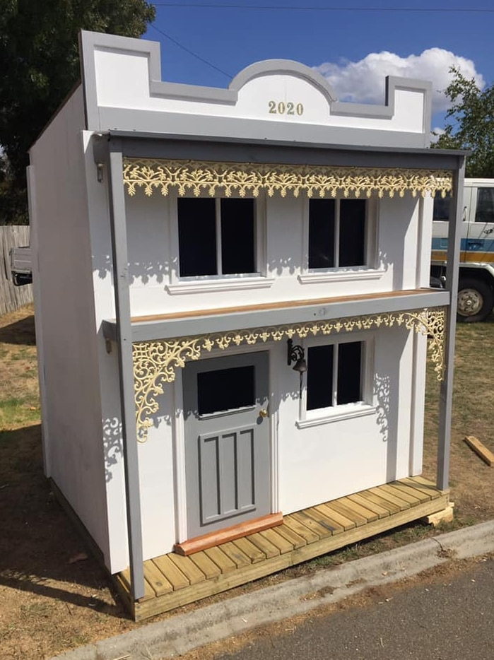 A designer cubby that is a replica of a two storey white townhouse with iron lace.