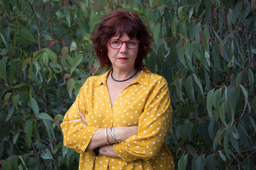 A woman stands of a gum tree wearing red glasses and a yellow shirt looking directly into the camera.