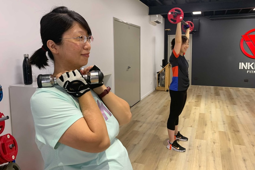 A woman lifting a dumbbell in a gym