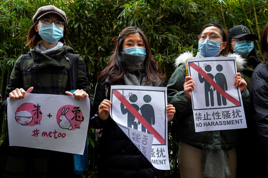 Supporters of Zhou Xiaoxuan hold banners while Zhou's lawsuit against a Chinese TV star was heard