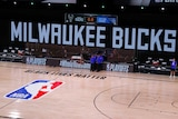 An empty NBA court, with screens that read 'MILWAUKEE BUCKS', 'NBA PLAYOFFS'. 'BLACK LIVES MATTER' is printed on the court