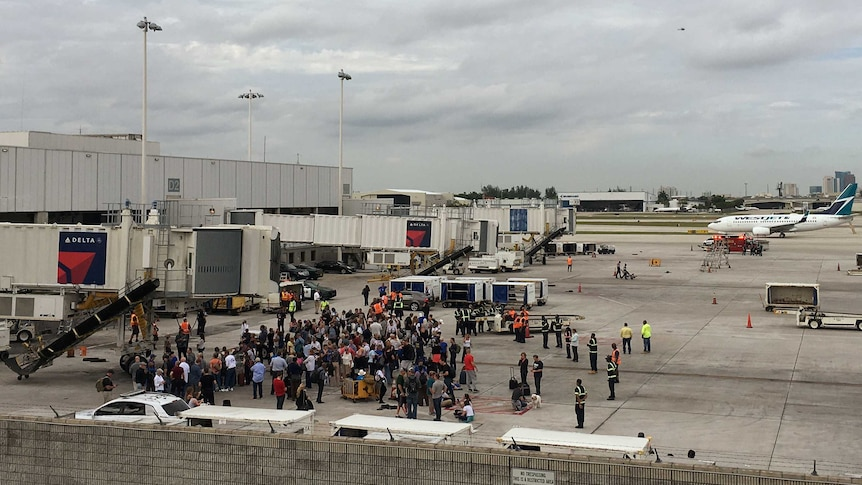 People rushed onto the tarmac at Fort Lauderdale international airport during the shooting (Image: Reuters/Zachary Fagenson)