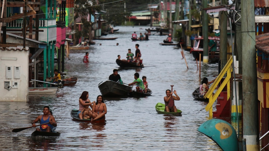 Residents float down the flooded street in boats between houses in Brazil.