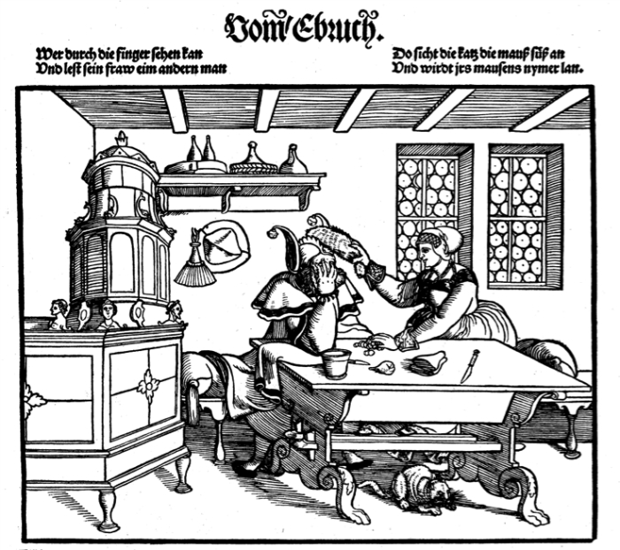 """A woodcut depicting a woman placing a """"fool's cap"""" on her husband."""