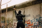 A man chisels into the Berlin Wall in November 1989.