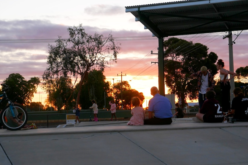 A man and a child watch a sunset at the skate park in Coolgardie.