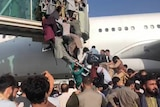 A group of people scramble to climb up stairs with a plane behind them.