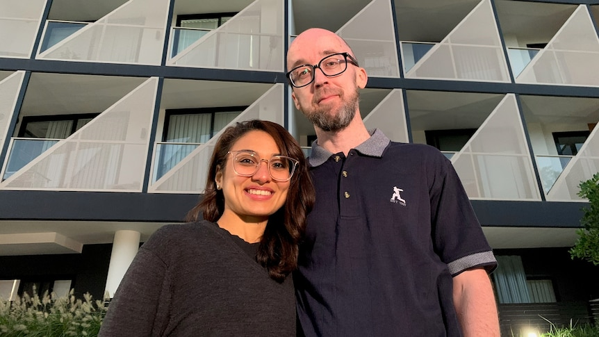A man and a woman stand in front of a new apartment block and smile.