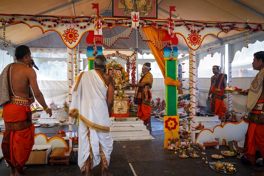 Several Hindu priests stand around a shrine during a ceremony