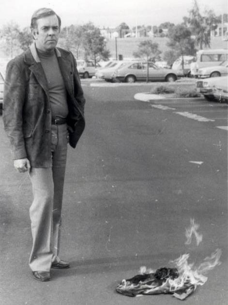 A black and white 1970s photo showing a man standing in a car park next to a burning flag on the ground.