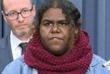 A woman in a purple scarf talking.