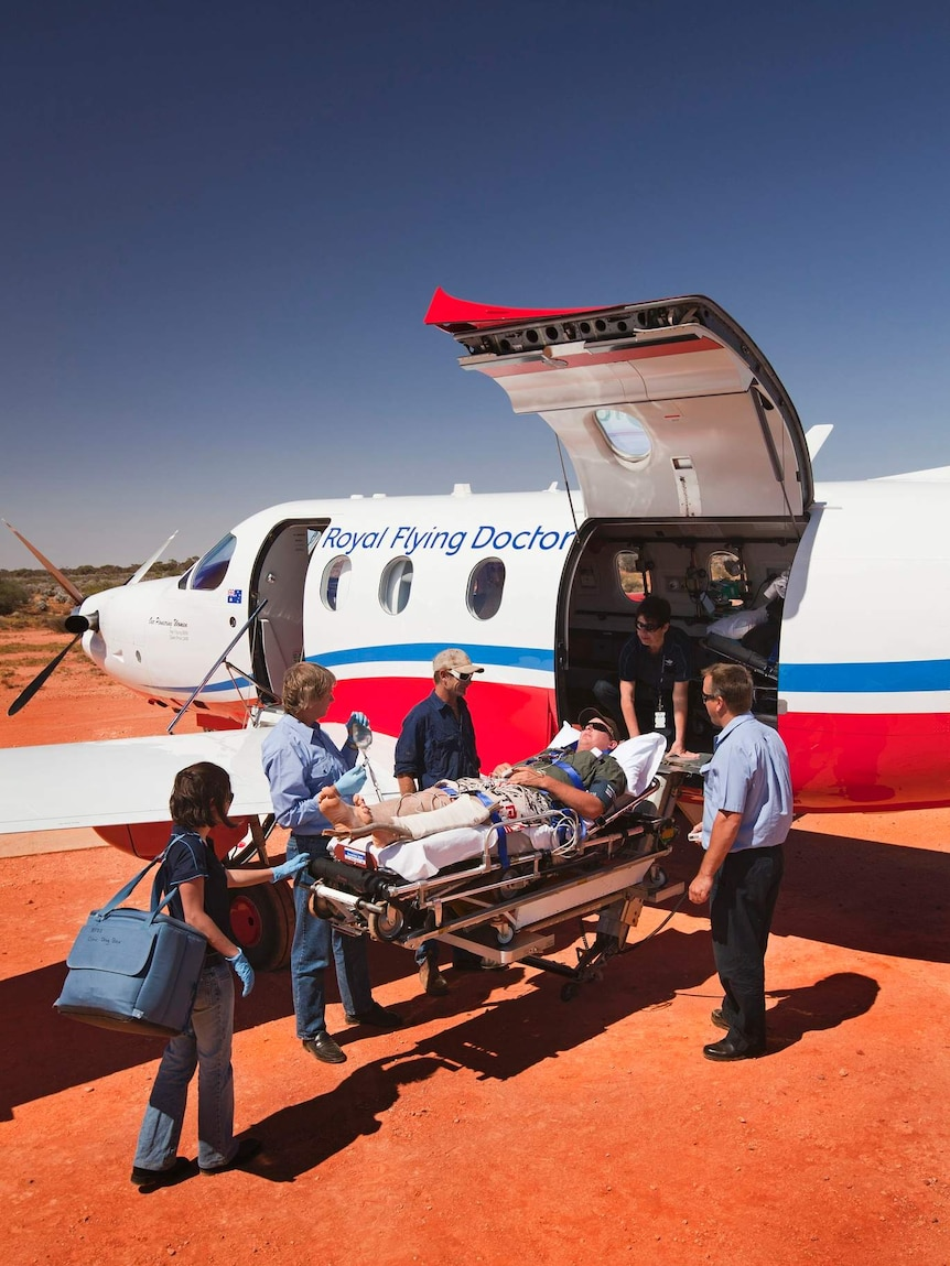 Mano n stretcher in desert being loaded onto small aircraft