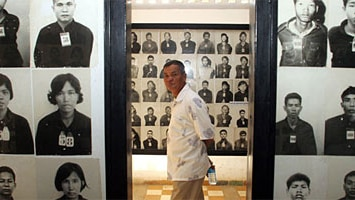 A Cambodian man walks through the former S-21 prison in Phnom Penh, surrounded by the photographs of former inmates.