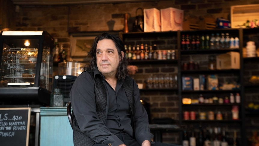 A man in black sits slouched on a chair in a bar