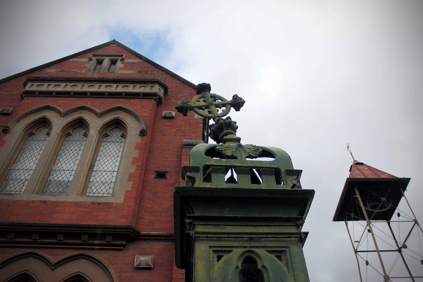 A view of a metal cross and the St Patrick's Catholic Church buildings in Ballarat.