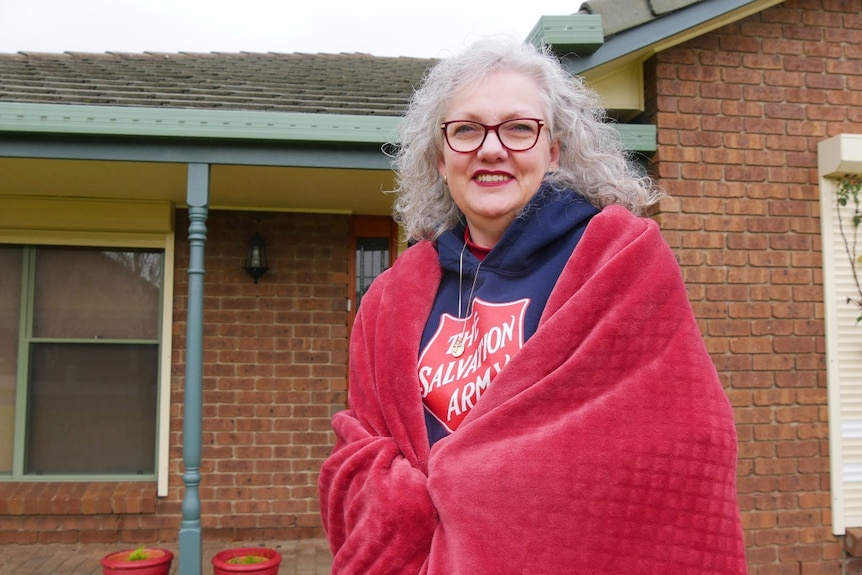 Woman standing in front of house wrapped in a blanket